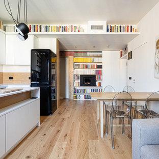 Immagine di una grande cucina scandinava con parquet chiaro, ante lisce, ante bianche, paraspruzzi marrone, paraspruzzi in legno, elettrodomestici neri, isola, pavimento beige e top bianco