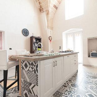 Immagine di una cucina mediterranea con lavello sottopiano, ante con bugna sagomata, ante bianche, top in marmo, pavimento in cementine, isola e pavimento beige