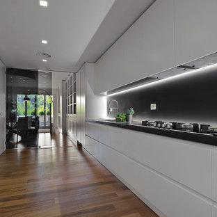 Ispirazione per una grande cucina lineare design con lavello da incasso, ante lisce, ante bianche, paraspruzzi nero, elettrodomestici da incasso, nessuna isola, pavimento marrone e top nero