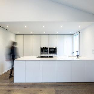 Esempio di una cucina parallela minimalista con isola, top bianco, ante lisce, ante bianche, elettrodomestici in acciaio inossidabile, parquet scuro e pavimento marrone