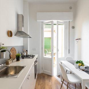 Ispirazione per una piccola cucina scandinava con ante lisce, ante bianche, paraspruzzi grigio, pavimento in legno massello medio, nessuna isola, pavimento marrone, lavello da incasso, paraspruzzi con lastra di vetro e elettrodomestici in acciaio inossidabile