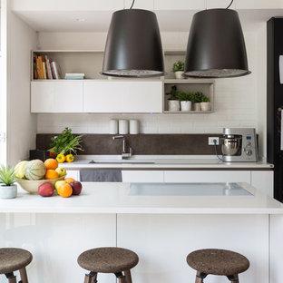 Idee per una cucina lineare minimal con lavello sottopiano, ante lisce, ante bianche, paraspruzzi grigio, isola e top bianco