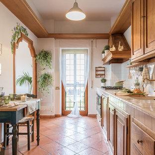 Ispirazione per una cucina mediterranea con lavello da incasso, ante con bugna sagomata, ante in legno scuro, paraspruzzi bianco, elettrodomestici da incasso, pavimento in terracotta, nessuna isola, pavimento arancione e top beige