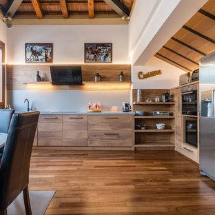 Ispirazione per una cucina abitabile minimal con ante in legno scuro, elettrodomestici in acciaio inossidabile, nessuna isola, ante lisce, paraspruzzi grigio, pavimento in legno massello medio e top grigio