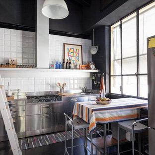 ミラノのインダストリアルスタイルのおしゃれなコの字型キッチン (フラットパネル扉のキャビネット、ステンレスキャビネット、白いキッチンパネル、シルバーの調理設備、黒い床、グレーのキッチンカウンター) の写真