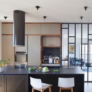 Foto di una cucina parallela contemporanea chiusa e di medie dimensioni con lavello da incasso, ante lisce, ante grigie, elettrodomestici da incasso, isola, pavimento marrone e top nero