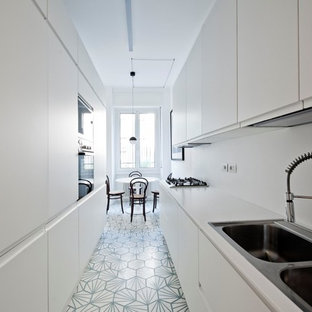Inspiration for a mid-sized scandinavian galley eat-in kitchen in Milan with flat-panel cabinets, white cabinets, white splashback, cement tiles, no island, a drop-in sink, panelled appliances and blue floor.