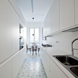 Zweizeilige, Mittelgroße Skandinavische Wohnküche ohne Insel mit flächenbündigen Schrankfronten, weißen Schränken, Küchenrückwand in Weiß, Zementfliesen, Einbauwaschbecken, Elektrogeräten mit Frontblende und blauem Boden in Mailand