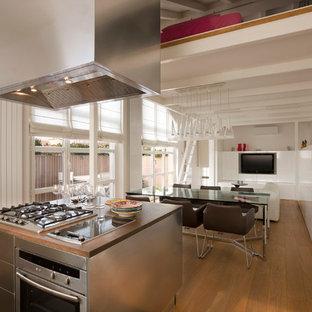 Ispirazione per una grande cucina design con ante lisce, ante in acciaio inossidabile, elettrodomestici in acciaio inossidabile, pavimento in legno massello medio e isola