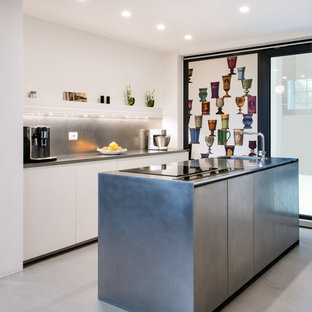 Mid-sized contemporary galley kitchen in Milan with an integrated sink, flat-panel cabinets, stainless steel cabinets, stainless steel benchtops, stainless steel appliances, concrete floors, with island, grey floor, grey splashback and grey benchtop.