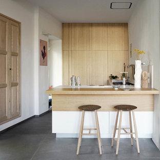 Idee per una cucina contemporanea con ante lisce, ante in legno chiaro, top in legno, pavimento in cemento, penisola e pavimento grigio