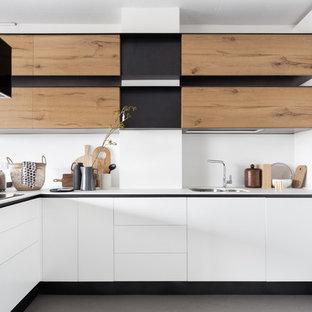 Idee per una cucina a L contemporanea di medie dimensioni con lavello sottopiano, ante lisce, ante bianche, paraspruzzi bianco, pavimento in cemento, penisola, pavimento grigio e top bianco