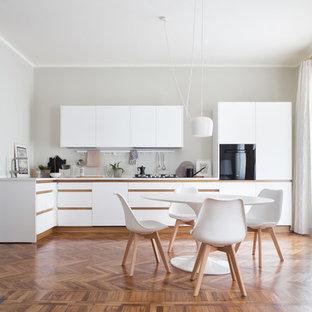 Esempio di una cucina scandinava di medie dimensioni con pavimento in legno massello medio, ante lisce, ante bianche, elettrodomestici neri, nessuna isola e pavimento marrone
