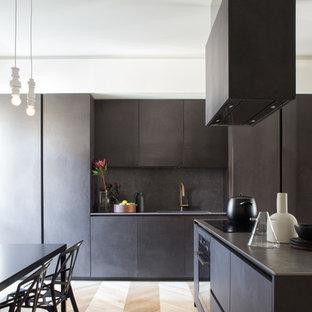Foto di una cucina contemporanea con ante lisce, ante nere, top in acciaio inossidabile, paraspruzzi nero, elettrodomestici neri, parquet chiaro, pavimento marrone e lavello integrato