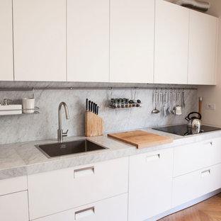 Idee per una cucina lineare design con ante bianche, nessuna isola, top bianco, lavello da incasso, ante lisce, paraspruzzi grigio, parquet chiaro e pavimento beige