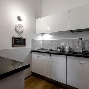 Esempio di una cucina a corridoio design con lavello da incasso, ante lisce, ante bianche, elettrodomestici in acciaio inossidabile, parquet chiaro e una penisola