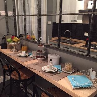 Exemple d'une petite cuisine parallèle industrielle fermée avec un évier posé, un placard à porte plane, des portes de placard blanches, un plan de travail en marbre, un électroménager en acier inoxydable et un sol en ardoise.