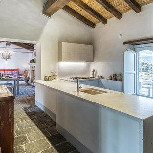 Ispirazione per una cucina a U mediterranea chiusa con lavello sottopiano, paraspruzzi grigio, penisola, pavimento grigio e top grigio