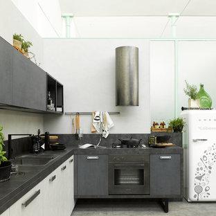 Esempio di una cucina a L industriale di medie dimensioni con lavello da incasso, elettrodomestici neri, ante lisce, ante grigie, pavimento in cemento, pavimento grigio, top nero e nessuna isola
