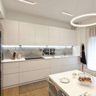 Mid-sized contemporary single-wall separate kitchen in Milan with an integrated sink, beaded inset cabinets, white cabinets, laminate benchtops, grey splashback, timber splashback, stainless steel appliances, light hardwood floors, no island, beige floor and white benchtop.