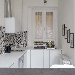 Foto di una piccola cucina ad U design con lavello da incasso, ante lisce, ante bianche, paraspruzzi multicolore, elettrodomestici da incasso, penisola e top bianco