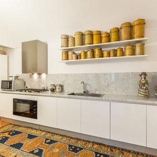 Ispirazione per una cucina lineare mediterranea con lavello da incasso, ante lisce, ante bianche, top in marmo, paraspruzzi grigio, paraspruzzi in lastra di pietra, elettrodomestici neri e parquet chiaro
