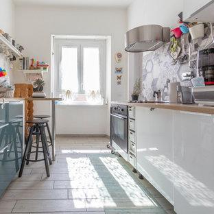 Ispirazione per una cucina parallela boho chic con ante lisce, ante bianche, top in legno, paraspruzzi grigio, elettrodomestici neri, pavimento beige e top beige