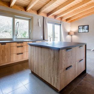Immagine di una cucina mediterranea con ante in legno scuro, isola, top nero, lavello a vasca singola, ante lisce, elettrodomestici da incasso e pavimento marrone