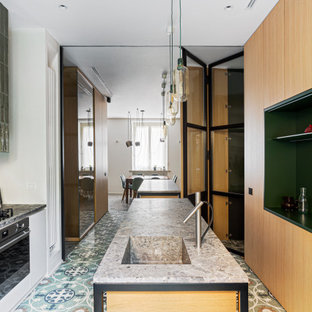 This is an example of a large modern galley eat-in kitchen in Milan with an integrated sink, beaded inset cabinets, light wood cabinets, marble benchtops, stainless steel appliances, marble floors, multiple islands, multi-coloured floor and grey benchtop.