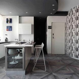 Ispirazione per un'ampia cucina a L design con ante lisce, ante bianche, elettrodomestici in acciaio inossidabile, pavimento in legno verniciato e isola