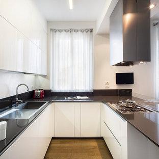 Immagine di una grande cucina contemporanea con lavello da incasso, ante lisce, ante bianche, paraspruzzi nero, paraspruzzi con lastra di vetro e pavimento in legno massello medio