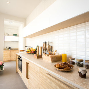 This is an example of a mid-sized scandinavian galley kitchen in Florence with flat-panel cabinets, light wood cabinets, limestone benchtops, white splashback and grey floor.