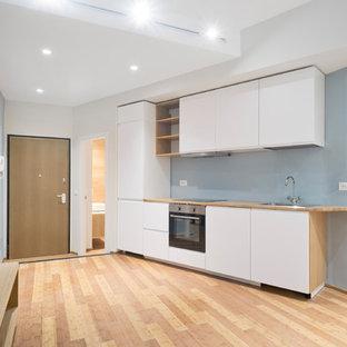 Diseño de cocina lineal, actual, pequeña, abierta, sin isla, con suelo de bambú, suelo marrón, fregadero encastrado, armarios con paneles lisos, puertas de armario blancas, encimera de madera, salpicadero azul y electrodomésticos de acero inoxidable