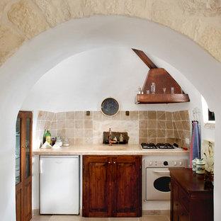 Idee per una cucina lineare country chiusa con lavello integrato, ante con bugna sagomata, ante in legno bruno, paraspruzzi beige, nessuna isola, pavimento beige e elettrodomestici bianchi