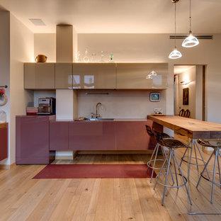 Idee per una cucina minimal di medie dimensioni con ante lisce, paraspruzzi beige, parquet chiaro, una penisola, ante beige e pavimento beige