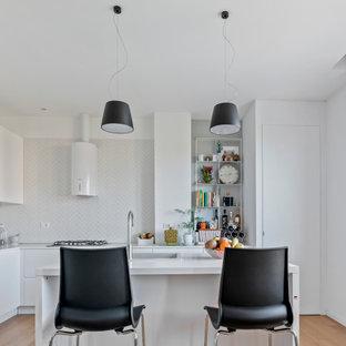 Ispirazione per una cucina a L contemporanea con lavello da incasso, ante lisce, ante bianche, pavimento in legno massello medio, isola, pavimento marrone e top bianco