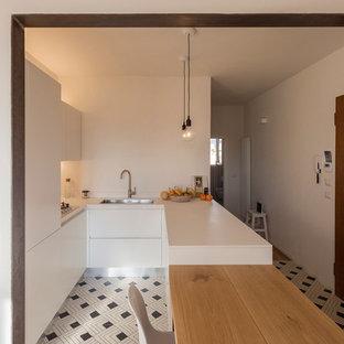 フィレンツェの中くらいのモダンスタイルのおしゃれなキッチン (ドロップインシンク、フラットパネル扉のキャビネット、白いキャビネット、人工大理石カウンター、セラミックタイルの床) の写真