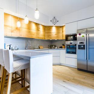 Immagine di una cucina minimal di medie dimensioni con ante lisce, ante bianche, paraspruzzi grigio, elettrodomestici in acciaio inossidabile, parquet chiaro, penisola, pavimento beige, lavello sottopiano e paraspruzzi con lastra di vetro