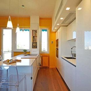 Foto di una cucina minimalista con lavello a vasca singola, ante lisce, ante bianche, paraspruzzi bianco, elettrodomestici bianchi, pavimento in laminato, penisola e top bianco