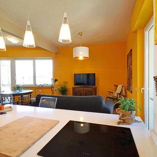 Immagine di una cucina minimalista con lavello a vasca singola, ante lisce, ante bianche, paraspruzzi bianco, elettrodomestici bianchi, pavimento in laminato, penisola e top bianco