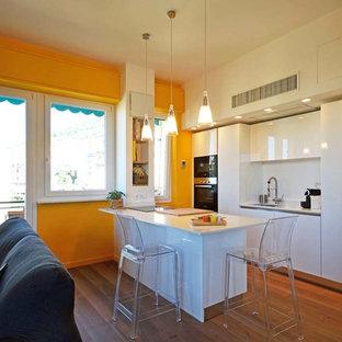 Idee per una cucina minimalista con lavello a vasca singola, ante lisce, ante bianche, paraspruzzi bianco, elettrodomestici bianchi, pavimento in laminato, penisola e top bianco