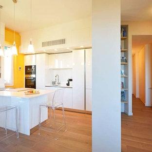 Esempio di una cucina minimalista con lavello a vasca singola, ante lisce, ante bianche, paraspruzzi bianco, elettrodomestici bianchi, pavimento in laminato, penisola e top bianco