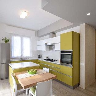 Foto di una cucina design con ante lisce, ante verdi, elettrodomestici in acciaio inossidabile, isola, top bianco, lavello a vasca singola e paraspruzzi bianco