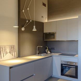 Diseño de cocina en L, minimalista, pequeña, abierta, con fregadero encastrado, armarios con paneles lisos, puertas de armario grises, encimera de laminado, suelo de baldosas de porcelana y encimeras grises