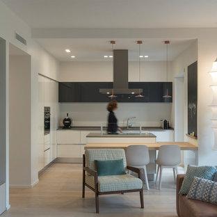 Immagine di una cucina contemporanea di medie dimensioni con lavello a doppia vasca, ante lisce, paraspruzzi bianco, elettrodomestici in acciaio inossidabile, parquet chiaro, isola, top grigio, ante bianche e pavimento beige