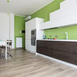 Ispirazione per una grande cucina contemporanea con paraspruzzi verde, elettrodomestici in acciaio inossidabile, parquet chiaro, nessuna isola, top bianco, ante lisce e ante in legno bruno