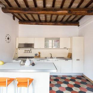 Idee per una cucina parallela mediterranea di medie dimensioni con ante lisce, ante bianche, top in acciaio inossidabile, paraspruzzi bianco, pavimento con piastrelle in ceramica, penisola e pavimento multicolore