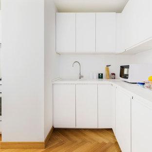 Immagine di una cucina a L contemporanea di medie dimensioni con ante lisce, ante bianche, paraspruzzi bianco, elettrodomestici bianchi, pavimento in legno massello medio, nessuna isola, pavimento marrone e top bianco
