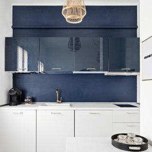 Offene, Einzeilige, Kleine Moderne Küche ohne Insel mit Laminat, weißem Boden, weißer Arbeitsplatte, Waschbecken, flächenbündigen Schrankfronten und weißen Schränken in Mailand