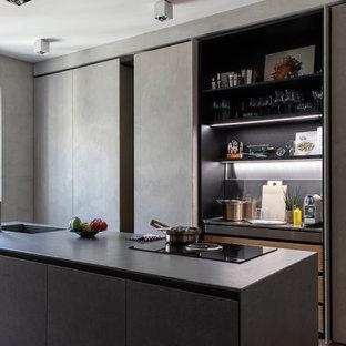 Esempio di una cucina design con ante lisce, ante grigie, pavimento in legno massello medio, un'isola, pavimento marrone e top grigio